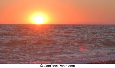 Sunset over the horizon with waves - Hot sun sank low over...