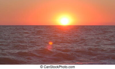 Sun as if leaning on wavering sea - Sunset over the sea, the...