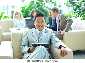 Asian business man with colleagues at a conference in the background