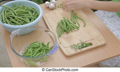 Trimming French green beans on wood - woman trimming French...