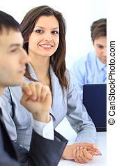 Closeup of a cute young businesswoman smiling in a meeting with her colleagues in background
