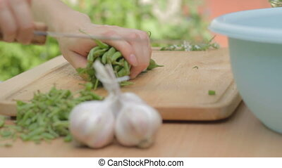 Slicing young green string beans in - Woman slicing young...