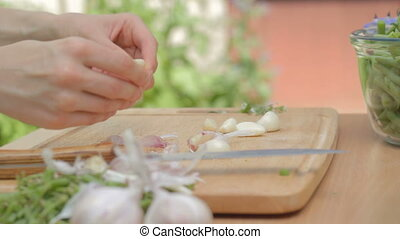Shucking garlic cloves from dry skins on wooden board...