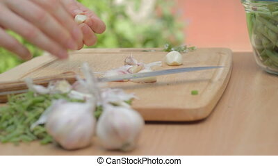 Clearing from dry husks every single clove of garlic on...