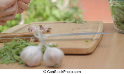 Shucking dry garlic cloves from skins on wooden board...