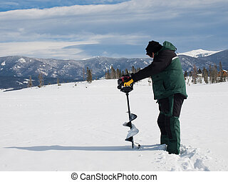Ice Fishing - Fisherman eith an auger on the frozen lake...