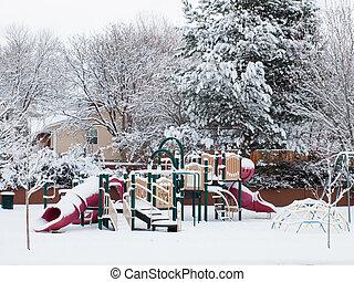 Kids playground in winter snow.