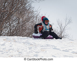 Boy Sleigh Riding - A young boy out playing in the snow.