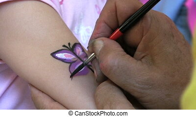 Painting A Butterfly On An Arm - A lady paints a pretty...