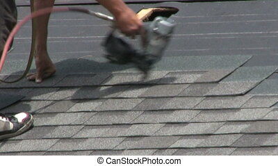 Laying Shingles - A man uses an automatic nail gun to lay...