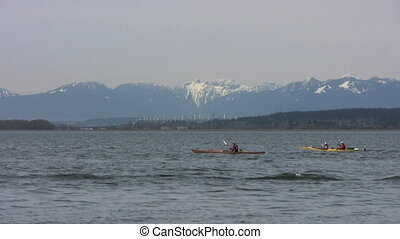 Kayaking In Front Of Mountains - A group of kayakers...