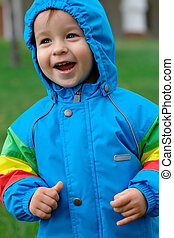 Happy baby in a raincoat - Portrait of a laughing baby in a...