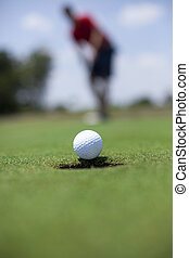 Putting the Golf Ball - A man putts a gold ball on the green...