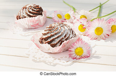 Chocolate cakes on the table with flowers