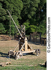 Medieval catapult - Medieval wooden catapult on a natural...