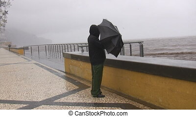 Man in the storm - Man is standing on the seafront in a...
