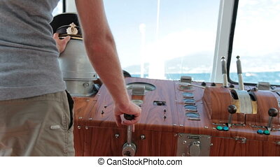 sailor controls boat in the wheelhouse