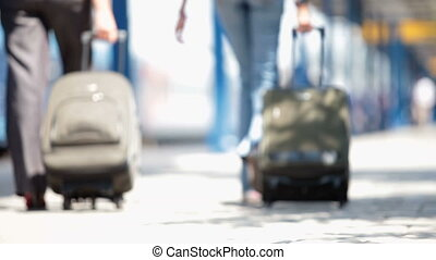 people with suitcases walk