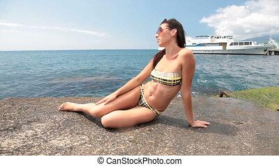 young girl in a bikini on pier