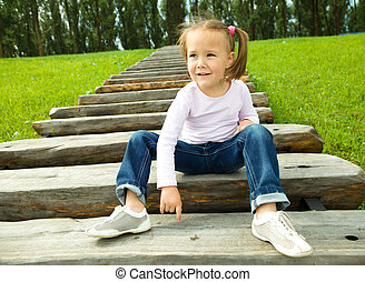 Cute little girl is sitting on stairs