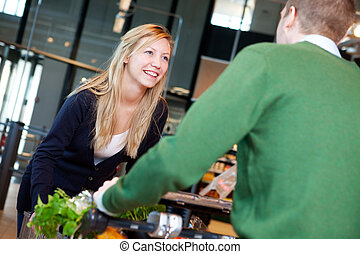 Playful Couple in Supermarket - A man pushing a woman...