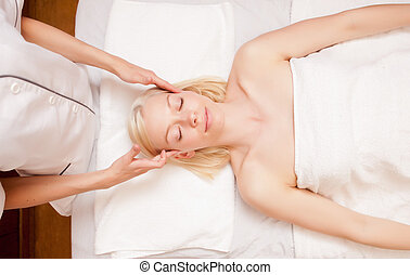 Spa Massage - A pretty young blonde woman receiving a scalp...
