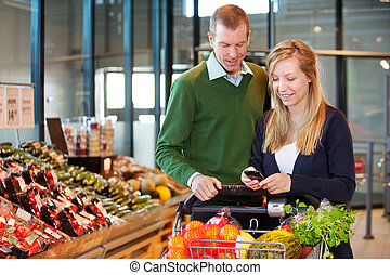 Couple Buying Groceries with List on Phone - A happy couple...