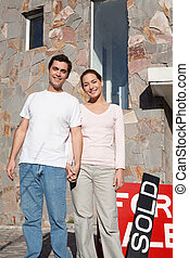 Happy young couple in front of their new home