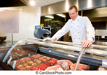 Fresh Meat Counter - A butcher at a fresh meat counter in a...