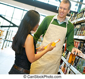 Helpful Grocery Store Clerk - Woman standing with smiling...