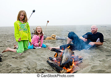 Beach Campfire - Father and two girls roasting marshmallows...
