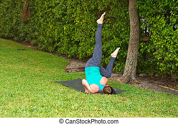woman doing Yoga pose fallen angel at base of tree