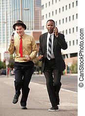 Hurrying Businessmen - Two businessmen on phones rush down...