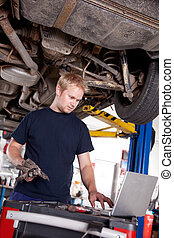 Mechanic with Laptop - A mechanic in a garage looking at a...