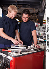 Mechanic at Work in Shop - A pair of mechanics working on a...