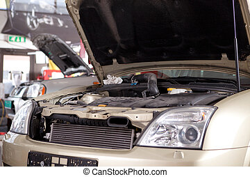 Car in Auto Repair Shop - A car with a hood up in a...