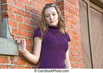 teenage girl - Teenage girl standing by old brick wall.