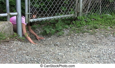 Kids Sneaking Under The Fence - Two cute Asian girls sneak...