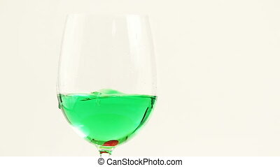 Green liquid in a glass - In a glass with liquid green throw...
