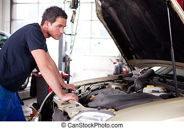 Car Problem - A young mechanic staring at a car, thinking