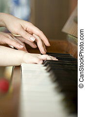 A child learns to play the piano