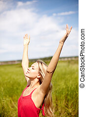 Surrender - Image of happy female with raised arms enjoying...