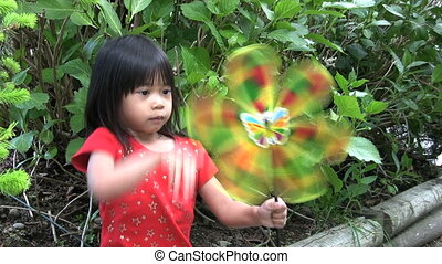 Little Asian Girl With A Pinwheel - A cute little Thai girl...