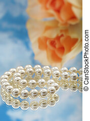 Elegant pearls over glass with clouds and rose very shallow...