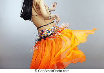 Backside of the belly dancer in traditional orange dress