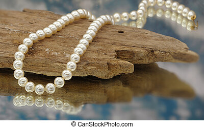 Elegant pearls with sky, drift wood, and reflection very...