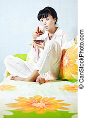 Coffee at the morning - Lady sitting on the bed and drinking...