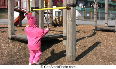 Little Girl Swings From Bar - A little 3 year old Asian girl...