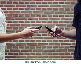 man and woman using cellphones to share files - young...