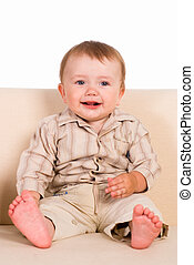 little boy sitting - young cute baby sitting on a sofa